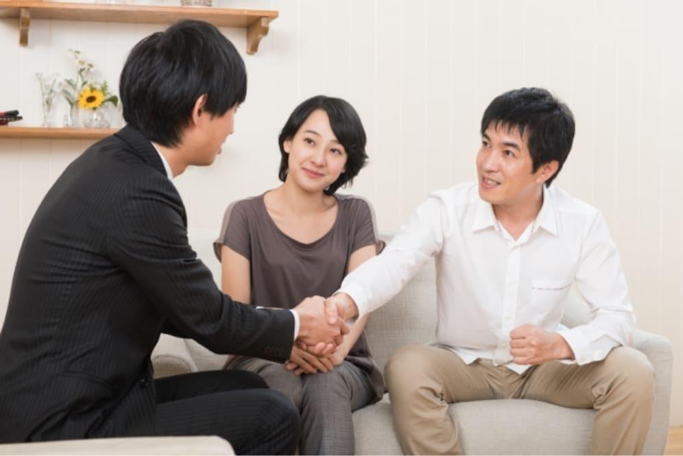 握手する男性と家族